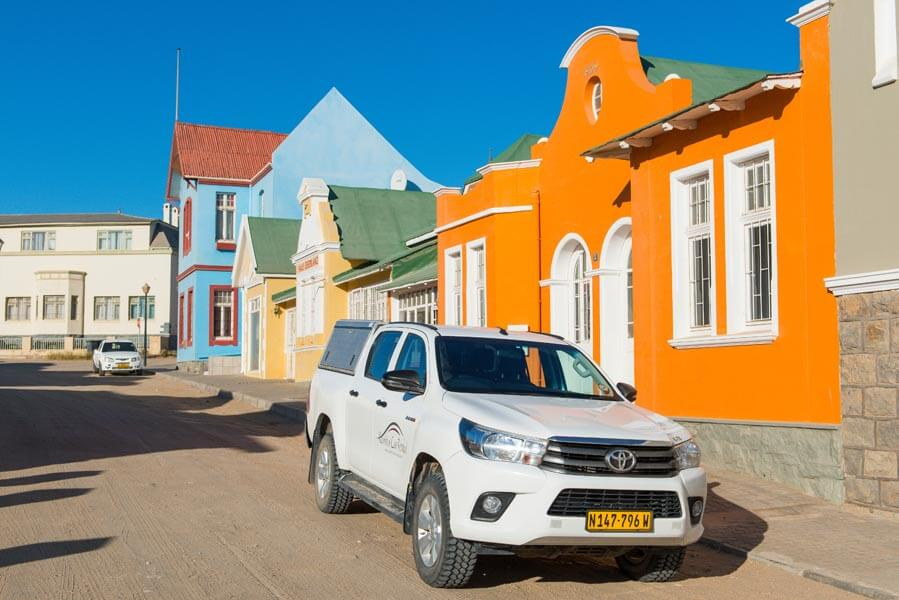 car infront of colourful buildings